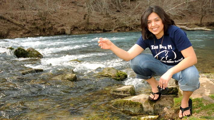 Amy Cervantes taking water samples.jpg