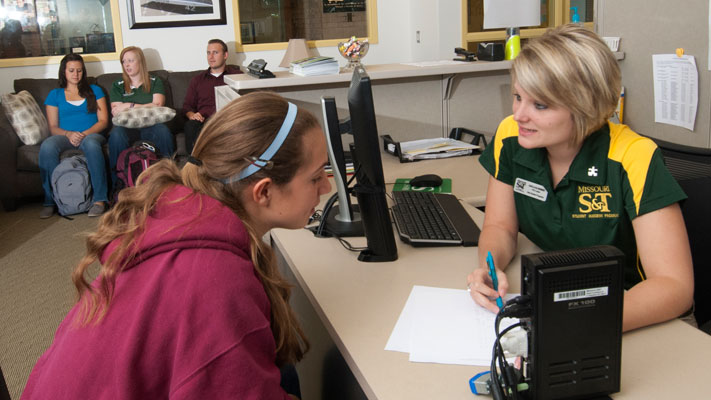 Margaret Eimer (left) checks in with Kayla Klossner, a success coach at the Burns & McDonnell Student Success Center. Photo by B.A. Rupert.