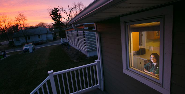 Julie Glenn, a senior in biological sciences and secretary of the Solar House Team, watches the sunset from the front window of her solar house.