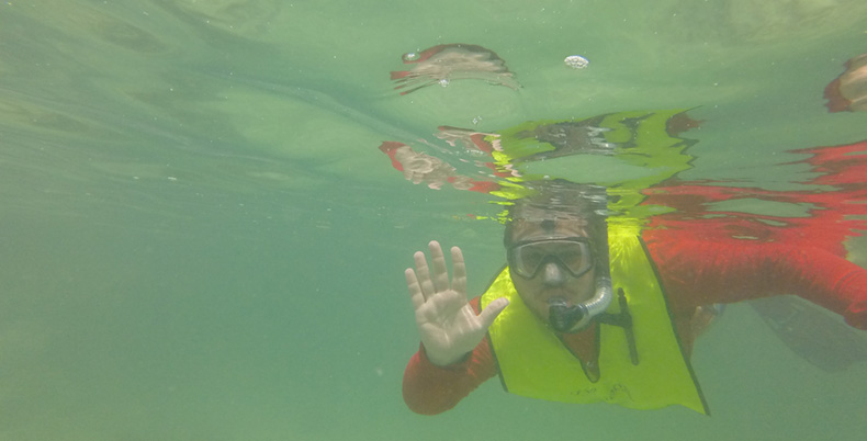 Justin Levy, who recently graduated with his bachelor's degree in geology, waves to the camera while snorkeling off the coast of San Salvador Island in the Bahamas while on a nine-day field study trip.