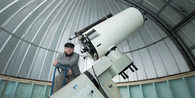 Ken Goss, a senior in computer science and computer engineering, poses with the S&T Observatory's 16-inch diameter telescope. Sam O'Keefe/Missouri S&T